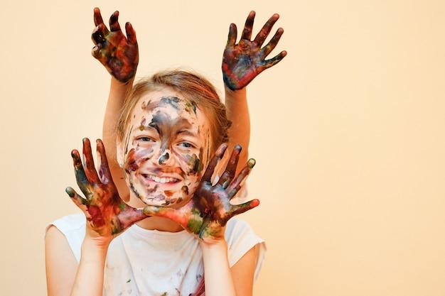 Bambina sorridente con la sorella dietro che fa le orecchie da coniglio con le mani in vernici colorate che sorride alla telecamera