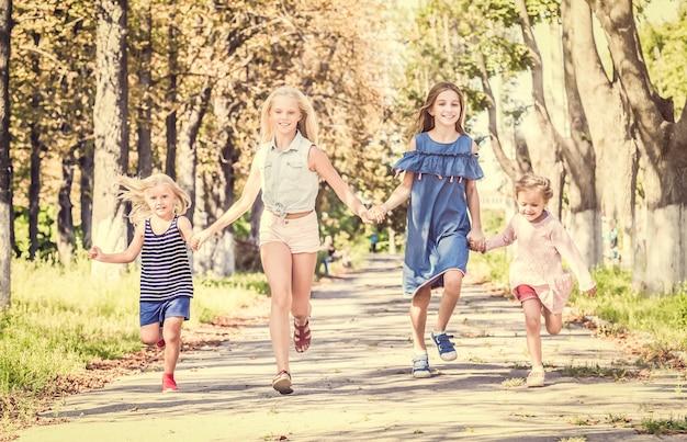 Piccole ragazze sorridenti che corrono sul vicolo di autunno del sole tenendosi per mano