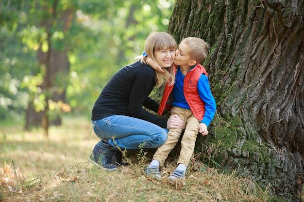 Piccolo figlio che abbraccia e bacia la sua mamma incinta sulla natura. ragazzo e donna incinta sorridente che cammina all'aperto nel parco verde. donna incinta che gode del tempo con il suo bambino