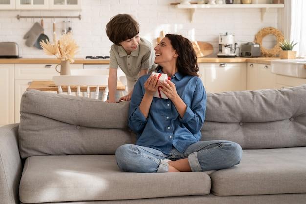 Il figlioletto fa una sorpresa di compleanno alla mamma salutando la madre con la festa della mamma che le regala una confezione regalo
