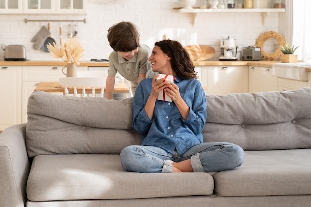 Il figlioletto fa una sorpresa di compleanno alla mamma salutando una madre con la festa della mamma che le regala una confezione regalo