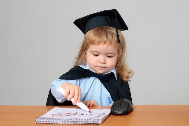 Piccolo bambino studente in abito da laurea e berretto al banco di scuola disegno nel taccuino con un pennarello