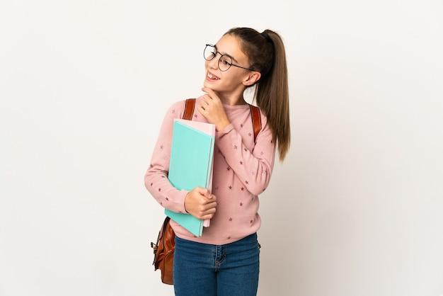 Piccola studentessa su sfondo isolato e alzando lo sguardo