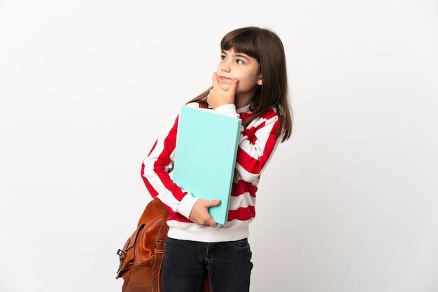 Piccola studentessa isolata su sfondo bianco che ha dubbi