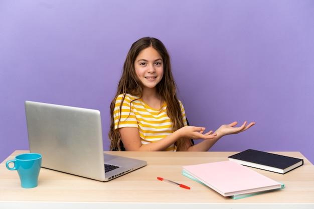 Piccola studentessa in un posto di lavoro con un laptop isolato su sfondo viola che allunga le mani di lato per invitare a venire