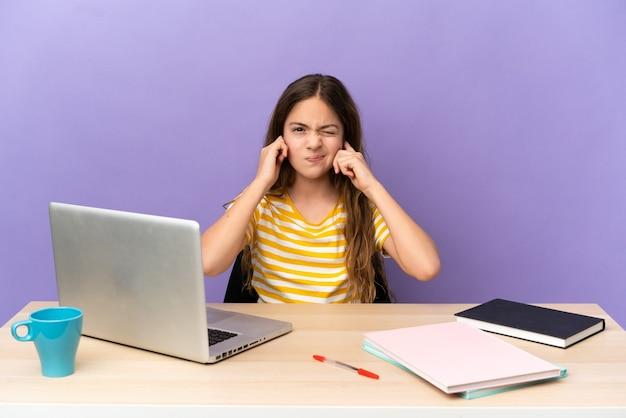 Piccola studentessa in un posto di lavoro con un laptop isolato su sfondo viola frustrata e che copre le orecchie