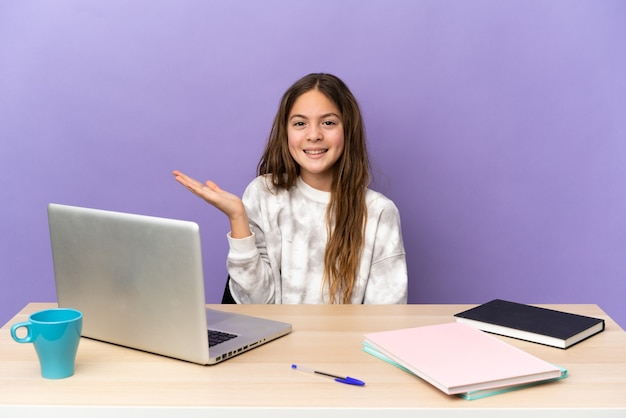 Piccola studentessa in un posto di lavoro con un laptop isolato su sfondo viola che tiene copyspace immaginario sul palmo per inserire un annuncio