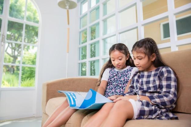 Le piccole ragazze dello studente godono del libro di lettura sul sofà a casa