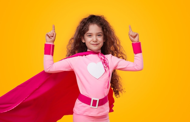 Piccola ragazza del supereroe che indica in su