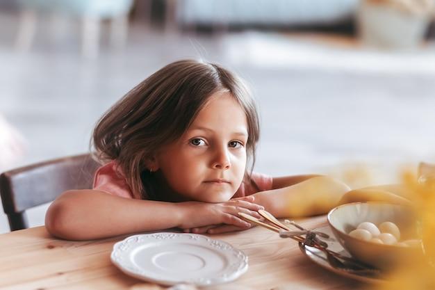 Una piccola dolce ragazza siede pensierosa al tavolo della cucina. bambino sognante