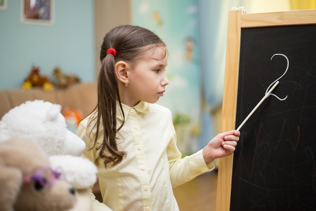 Piccolo insegnante. la bella ragazza sta insegnando i giocattoli a casa sulla lavagna. istruzione domestica prescolare.