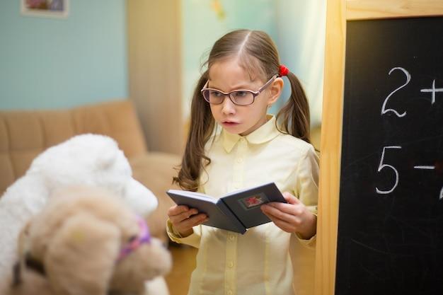 Piccolo insegnante in bicchieri. la bella ragazza sta insegnando i giocattoli a casa sulla lavagna. istruzione domestica prescolare.