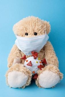 Piccolo orsacchiotto in maschera medica che tiene il modello del coronavirus