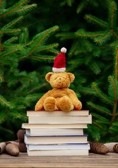 Giocattolo del piccolo orsacchiotto in cappello e libri di santa claus sulla tavola di legno con i rami attillati su fondo