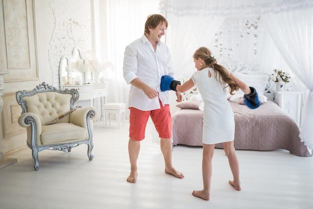 La piccola ragazza adolescente combatte con suo padre usando i guantoni da boxe mentre si trova in un salotto chic con un bellissimo arredamento