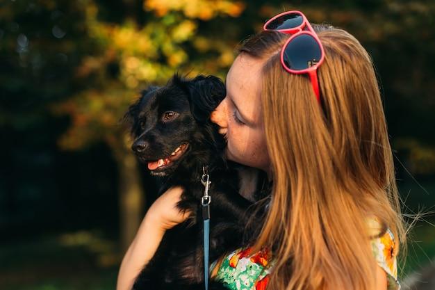 Bambina tenera in un vestito estivo che bacia il suo animale domestico con amore