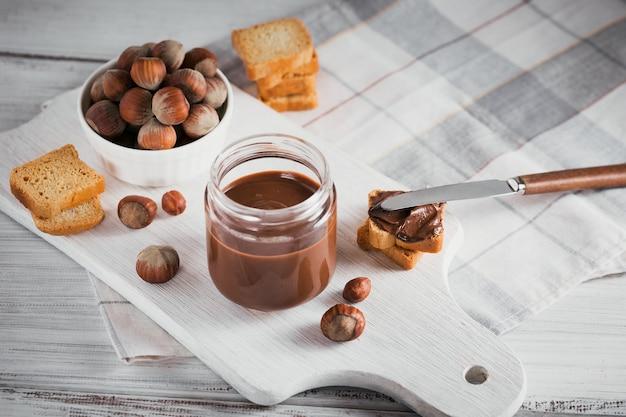 Piccoli toast con cioccolato dolce alla nocciola da spalmare per colazione su superficie di legno bianca