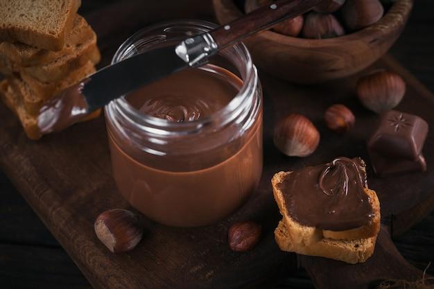 Piccoli toast con crema di cioccolato dolce alla nocciola per colazione.