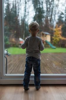 Piccolo ragazzo del bambino che fa una pausa una porta di vetro che guarda fuori in una giornata piovosa