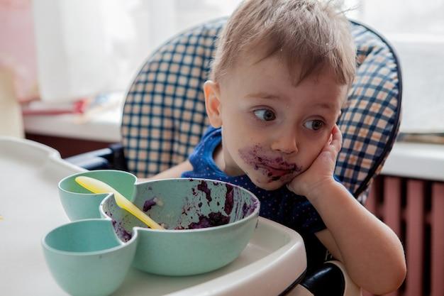 Piccolo ragazzo del bambino con la faccia sporca che mangia mirtillo fresco indoor, vitamine e salute