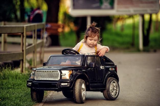 Piccola ragazza del bambino che guida l'automobile radiocomandata del cabriolet nero del giocattolo grande sulla strada nel parco in estate e che osserva giù con fondo vago