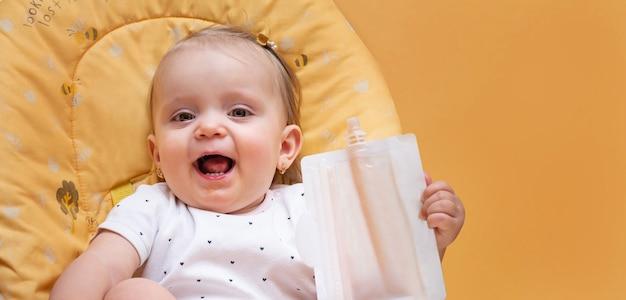 La piccola ragazza del bambino mangia i frullati con una miscela di frutta
