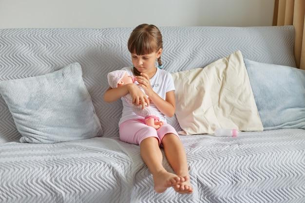 Piccola bambina che allatta la sua bambola con la bottiglia, affascinante bambina con i capelli scuri e le trecce che indossa una maglietta bianca e un corto rosa che gioca con il giocattolo al coperto