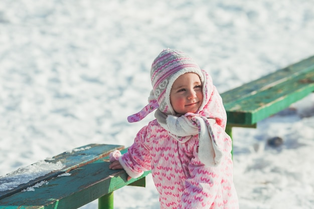 La piccola bambina sta facendo i primi passi sulla neve, camminando in una giornata di sole invernale