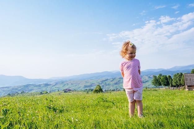 Piccola ragazza del bambino che funziona in un bello campo