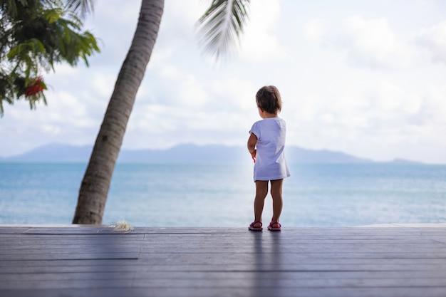 La bambina in un abito bianco guarda il mare mentre si trova sul pavimento di legno all'esterno. vista posteriore. focalizzazione morbida