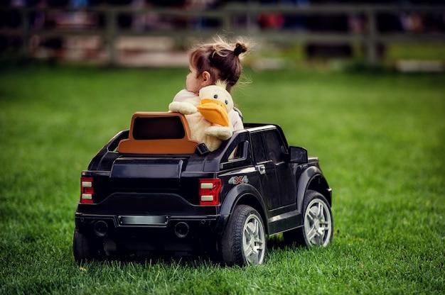 Piccola ragazza del bambino con lo zaino a forma di anatra sulla schiena guida grande giocattolo cabriolet nero auto radiocomandata su erba verde nel parco in estate con sfondo sfocato