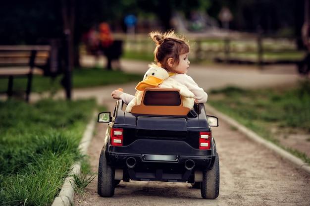 Piccola ragazza del bambino con lo zaino a forma di anatra sulla schiena che guida un'auto radiocomandata cabriolet nera grande giocattolo sulla strada nel parco in estate e guardando lateralmente con sfondo sfocato