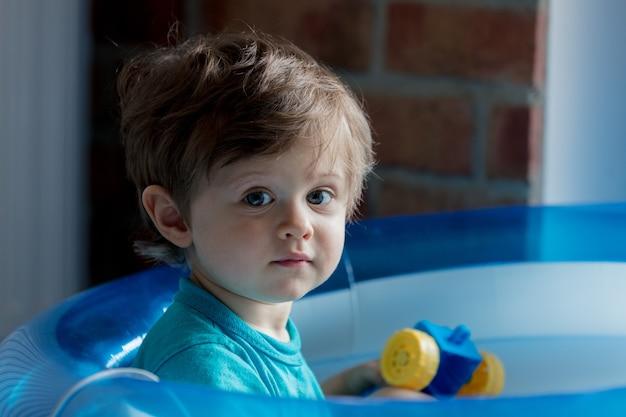 Little toddler si gioca in una piscina gonfiabile