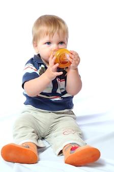 Il piccolo bambino si siede e beve l'acqua dalla bottiglia arancione