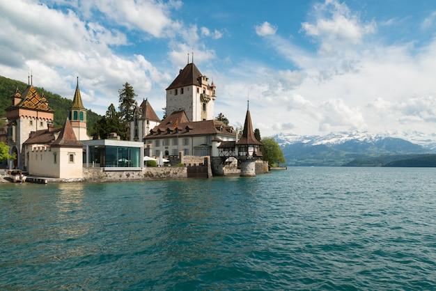 La piccola torre del castello di oberhofen nel lago thun con le montagne su fondo in svizzera