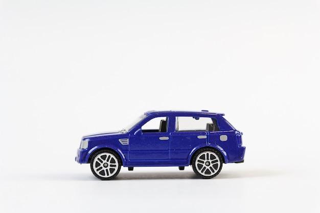 Una piccola auto giocattolo blu con sfondo bianco.