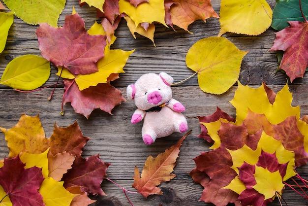 Maialino rosa giocattolo tra le foglie autunnali colorate luminose su un fondo rustico in legno