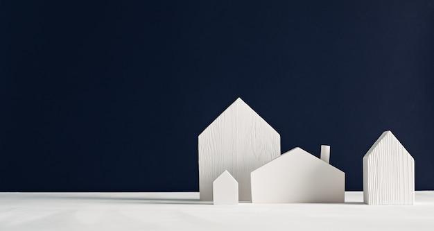 Piccole case giocattolo di legno bianche su uno sfondo nero minimalista design decorativo scandinavo