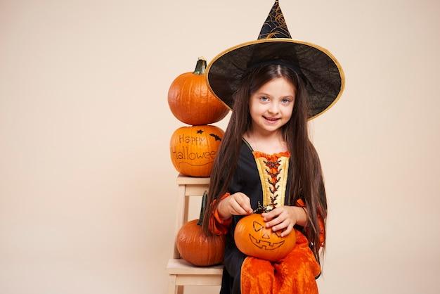 Piccola strega con la zucca di halloween