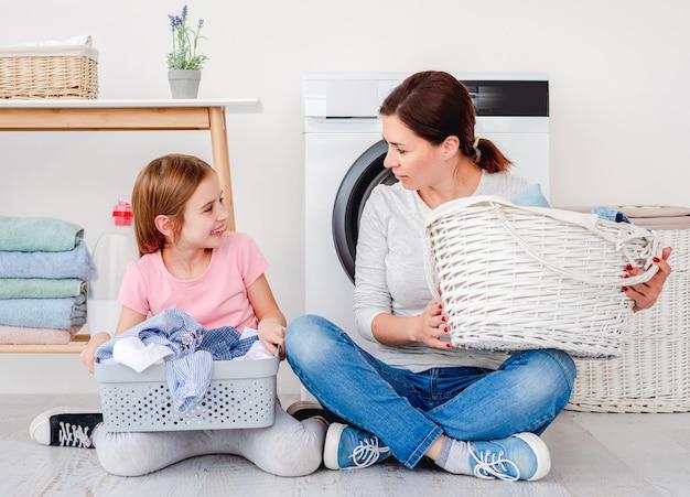 Piccola donna che aiuta la madre con un mucchio di vestiti durante il lavaggio del cestino della holding