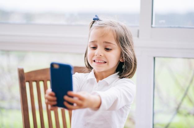 Una piccola donna scatta una foto con lo smartphone del telefono cellulare a casa