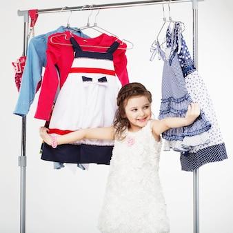 Piccola donna che prova nuovi vestiti su bianco
