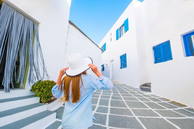 Piccola donna che cammina su una strada greca