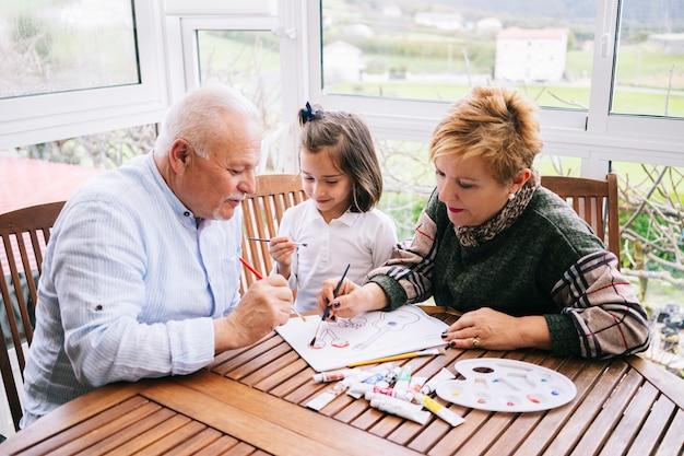 Una piccola donna con i suoi nonni dipinge alcuni disegni sulla terrazza della sua casa con pittura ad acquerello