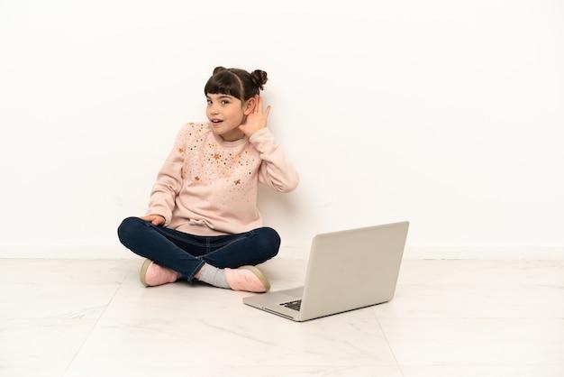 Piccola donna con un laptop seduto sul pavimento ascoltando qualcosa mettendo la mano sull'orecchio