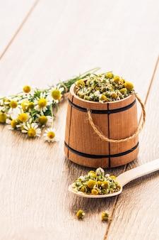 Piccola botte di legno con fiori secchi di camomilla e bouquet di camomille fresche su tavole di legno con spazio per le copie