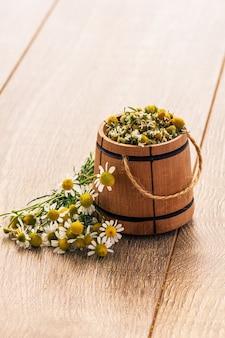 Piccola botte di legno con fiori secchi di camomilla e bouquet di camomille fresche su assi di legno.
