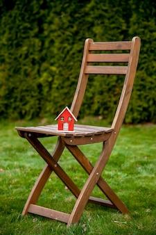 Piccola casa di legno su una sedia in un giardino in primavera