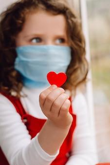 Bambina con maschera per prevenire la diffusione dell'infezione di covid-19, con in mano un piccolo cuore rosso, seduta sul davanzale della finestra a casa. coronavirus epidemico a diffusione pandemica. messa a fuoco selettiva.