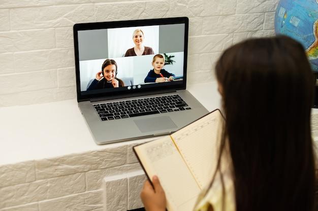Bambina guardando lo schermo del laptop con espressione di sorpresa ed eccitazione. bambina intelligente e sorridente che prende appunti. comunicazione nel concetto di business.